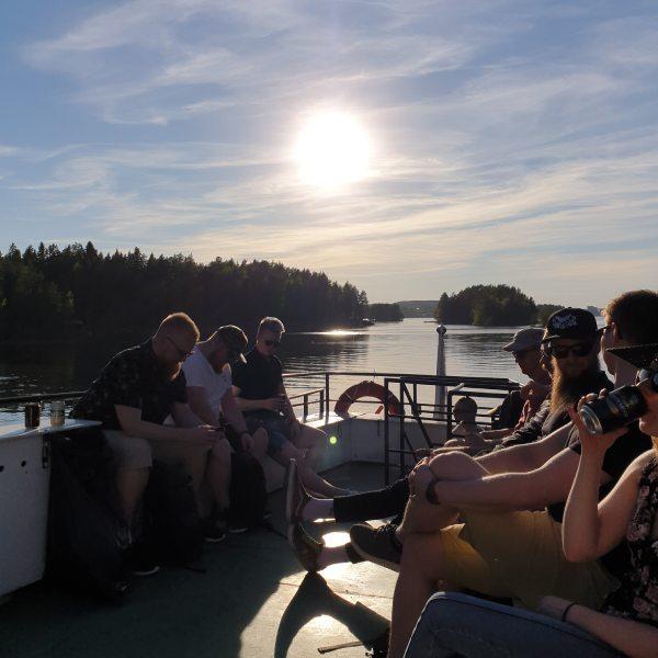 Hurja Solutions kesäpäivä työntekijät laivan kannella auringonlaskussa.